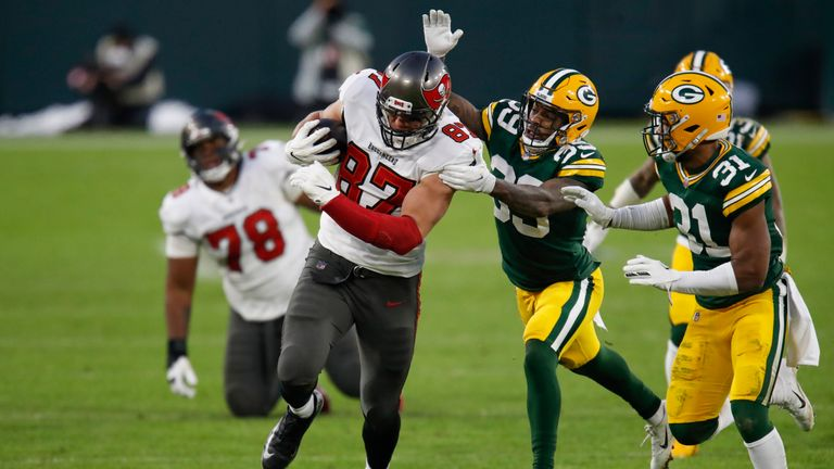 Green Bay Packers' Ka'dar Hollman (29) and Adrian Amos try to stop Tampa Bay Buccaneers' Rob Gronkowski during the second half of the NFC championship NFL football game in Green Bay, Wis., Sunday, Jan. 24, 2021. (AP Photo/Matt Ludtke)