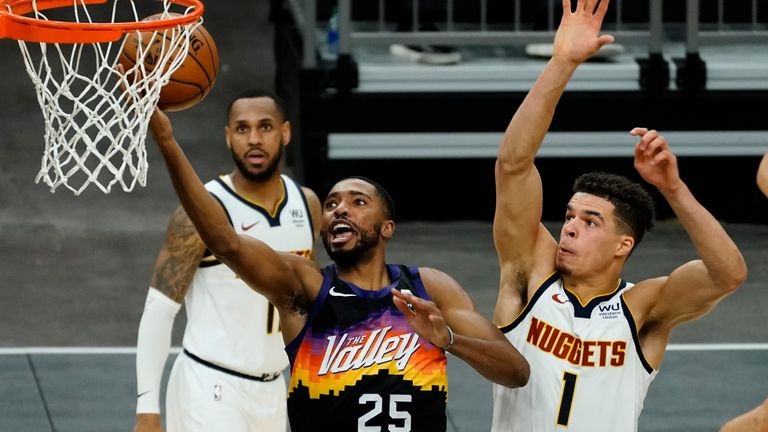 Phoenix Suns forward Mikal Bridges (25) drives past Denver Nuggets forward Michael Porter Jr. (1) during the second half of an NBA basketball game Saturday, Jan. 23, 2021, in Phoenix.