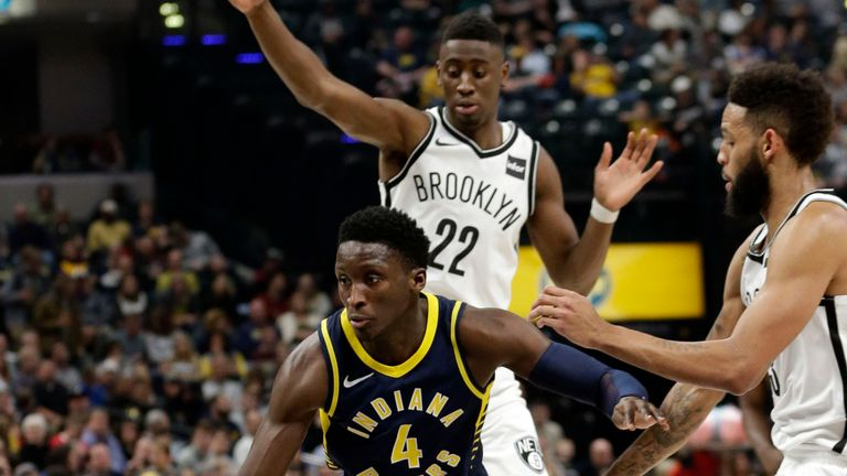 Indiana Pacers guard Victor Oladipo goes through Brooklyn Nets defender Caris LeVert