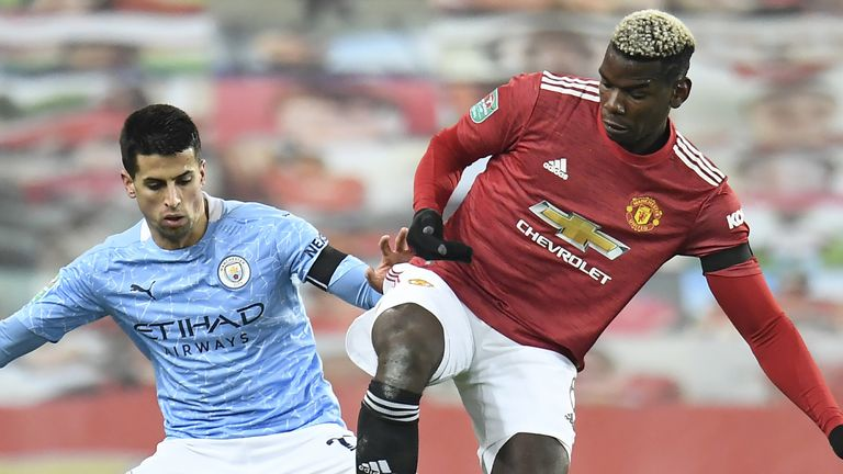 Paul Pogba is challenged by Joao Cancelo during the Carabao Cup semi-final