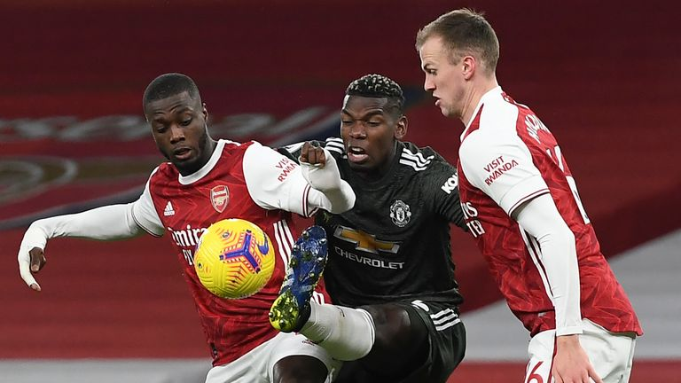Paul Pogba is challenged by Arsenal's Nicolas Pepe and Rob Holding (AP)