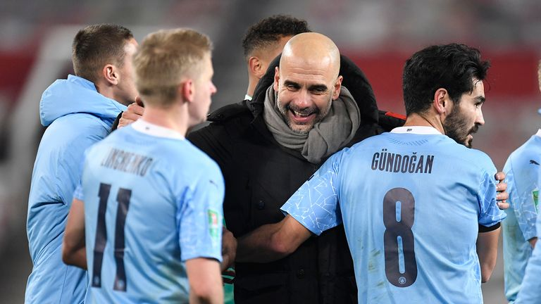Manchester City's head coach Pep Guardiola, right, congratulates his players after the English League Cup semifinal soccer match between Manchester United and Manchester City at Old Trafford in Manchester, England, Wednesday, Jan. 6, 2021