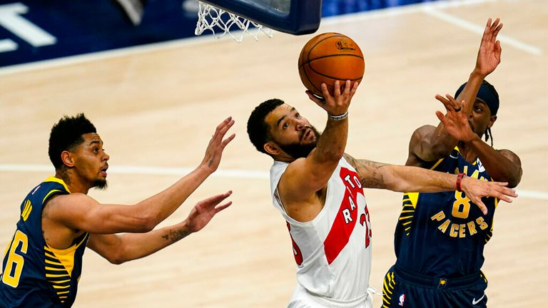 AP - Toronto Raptors guard Fred VanVleet (23) shoots between Indiana Pacers guard Jeremy Lamb (26) and guard Justin Holiday (8) during the second half