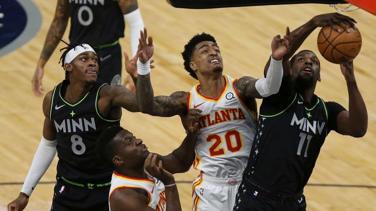Minnesota Timberwolves' Naz Reid (11) grabs a rebound ball against Atlanta Hawks' John Collins (20) during the first half of an NBA basketball game Friday, Jan. 22, 2021, in Minneapolis. (AP Photo/Stacy Bengs)