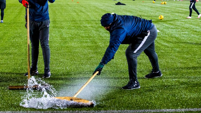 SNS - Ground staff sweep rain off the pitch ahead of the postponed Scottish Premiership match between Livingston and Aberdeen at the Tony Macaroni Arena