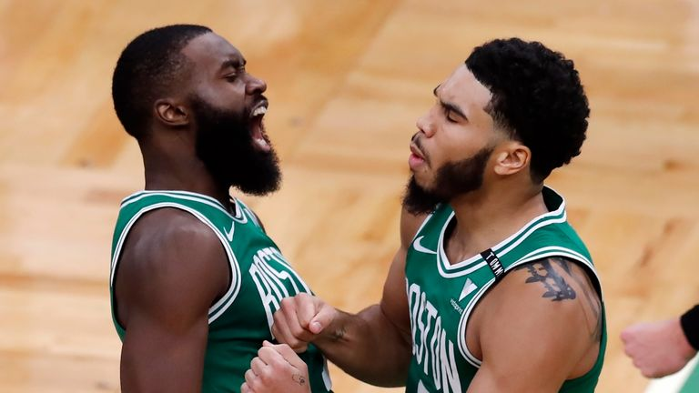 Boston Celtics' Jayson Tatum celebrates with Jaylen Brown after making the go-ahead basket with less than a second on the clock during the second half of an NBA basketball game against the Milwaukee Bucks