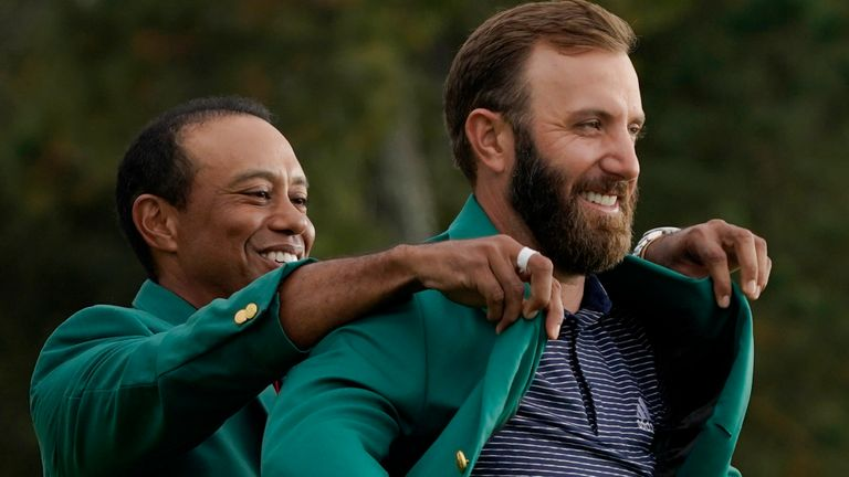 Tiger Woods helps Masters... champion Dustin Johnson with his green jacket after his victory at the Masters golf tournament Sunday, Nov. 15, 2020, in Augusta, Ga. (AP Photo/Charlie Riedel)
