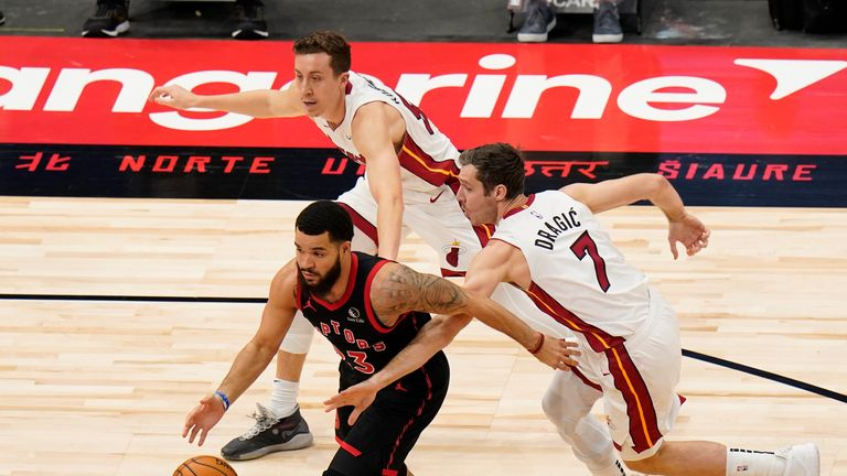Toronto Raptors guard Fred VanVleet (23) drives past Miami Heat guard Duncan Robinson (55) and guard Goran Dragic (7) during the first half of an NBA basketball game Friday, Jan. 22, 2021, in Tampa, Fla. (AP Photo/Chris O'Meara)