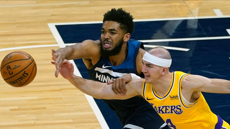 Minnesota Timberwolves' Karl-Anthony Towns, left, and Los Angeles Lakers' Alex Caruso battle for the ball in the first half of an NBA basketball game, Tuesday, Feb. 16, 2021, in Minneapolis.