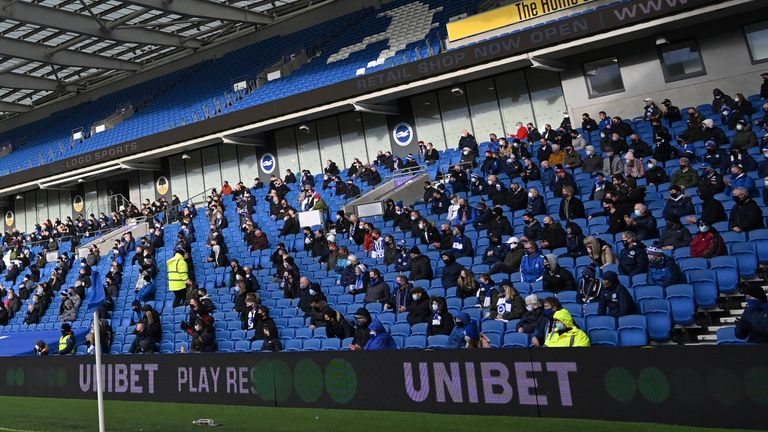 Fans sit socially distanced during the Premier League match between Brighton and Hove Albion and Sheffield United