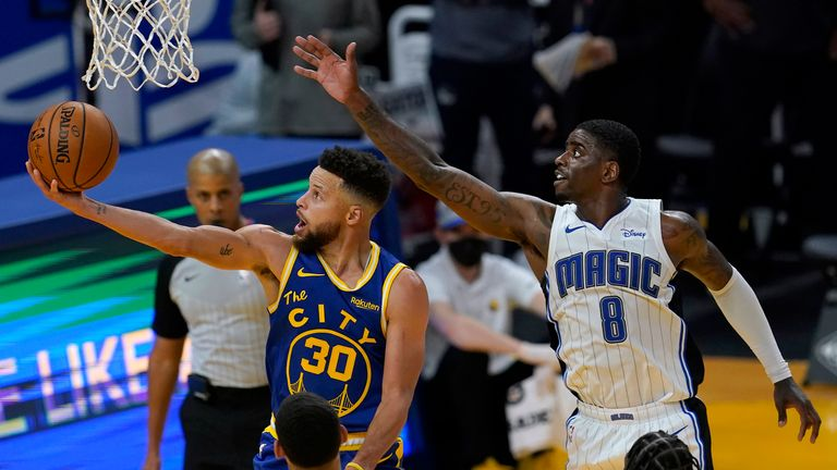 Golden State Warriors guard Stephen Curry shoots in front of Orlando Magic forward Dwayne Bacon