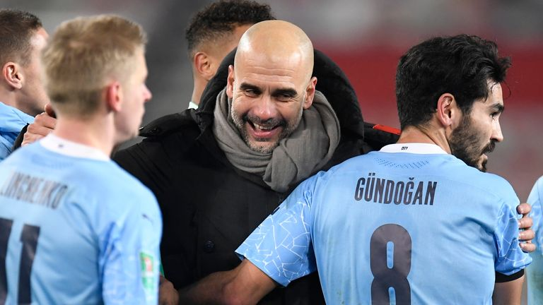 Manchester City's head coach Pep Guardiola, right, congratulates his players after the English League Cup semifinal soccer match between Manchester United and Manchester City at Old Trafford in Manchester, England, Wednesday, Jan. 6, 2021. (Peter Powell/Pool via AP)