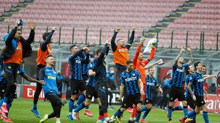 Inter players celebrate their 3-0 win at the end of the Serie A soccer match between AC Milan and Inter Milan, at the Milan San Siro Stadium, Italy, Sunday, Feb. 21, 2021. (AP Photo/Antonio Calanni)
