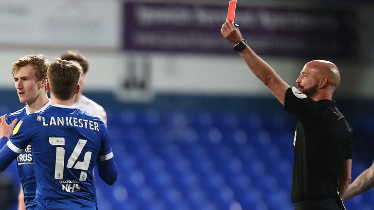 Flynn Downes of Ipswich Town is shown a red card by referee Darren Drysdale against Northampton