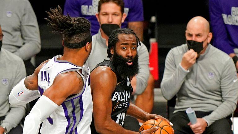 AP - Sacramento Kings center Richaun Holmes, left, defends Brooklyn Nets guard James Harden