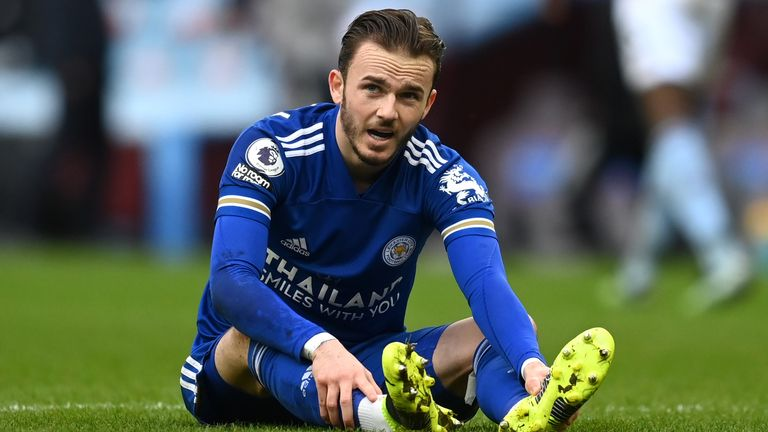 James Maddison holds his foot as he sits injured