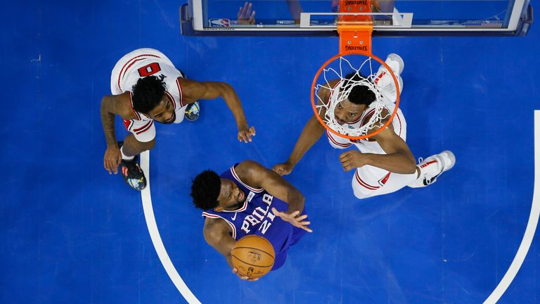 Philadelphia 76ers' Joel Embiid goes up for a shot between Chicago Bulls' Coby White and Wendell Carter Jr.