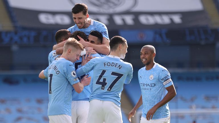 John Stones is mobbed by teammates after putting Man City back in front (AP)