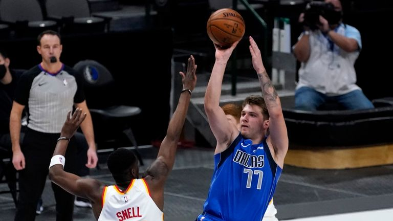 Atlanta Hawks' Tony Snell defends as Dallas Mavericks' Luka Doncic goes up to sink