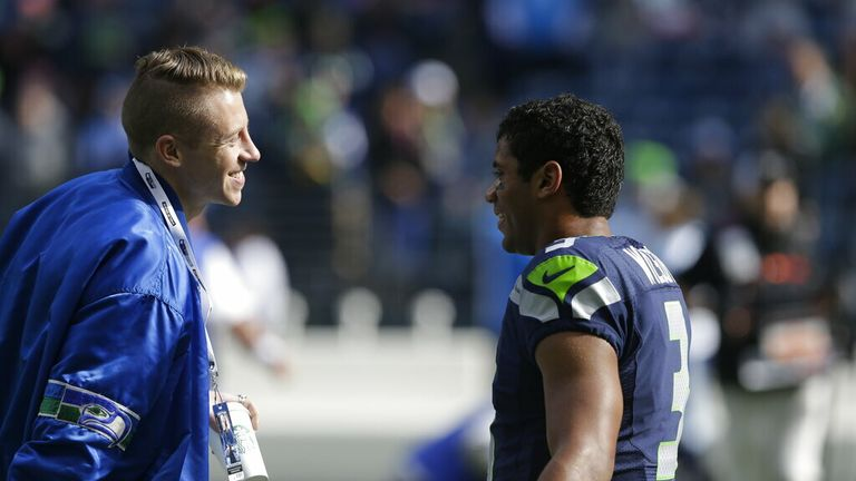 AP - Seattle hip hop and rap singer Macklemore greets Seattle Seahawks quarterback Russell Wilson