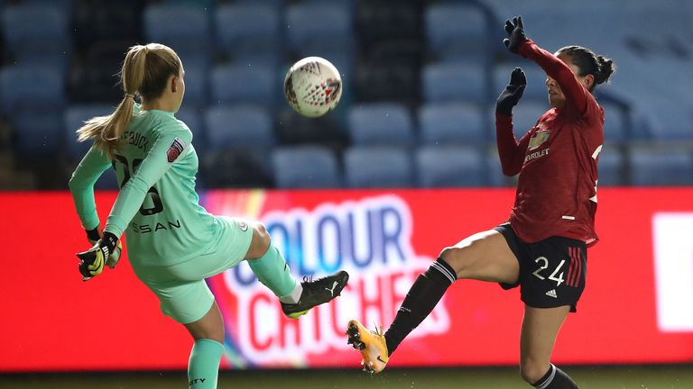 Ellie Roebuck clears the ball ahead of the onrushing Christen Press