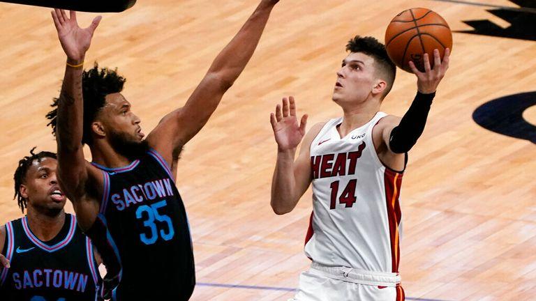 AP - Sacramento Kings forward Marvin Bagley III, front left left, challenges the shot of Miami Heat guard Tyler Herro
