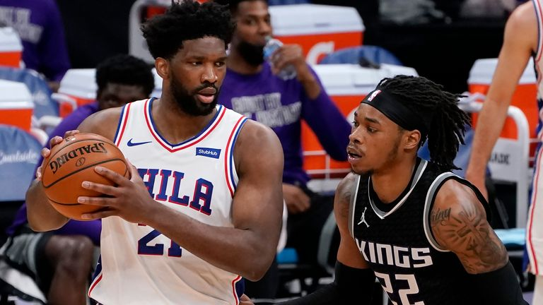 Philadelphia 76ers center Joel Embiid, left, looks to pass against Sacramento Kings center Richaun Holmes, right, during the second half of an NBA basketball game in Sacramento, Calif., Tuesday, Feb. 9, 2021. The 76ers won 119-111.