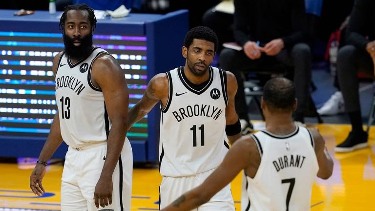 Brooklyn Nets guard Kyrie Irving, middle, gathers with guard James Harden (13) and forward Kevin Durant (7) during the second half of an NBA basketball game against the Golden State Warriors in San Francisco, Saturday, Feb. 13, 2021. (AP Photo/Jeff Chiu)