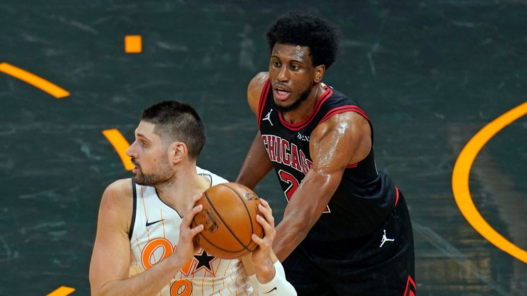Orlando Magic center Nikola Vucevic (9) looks to pass the ball as he is guarded by Chicago Bulls forward Thaddeus Young, right, during the first half of an NBA basketball game, Friday, Feb. 5, 2021, in Orlando, Fla. (AP Photo/John Raoux)