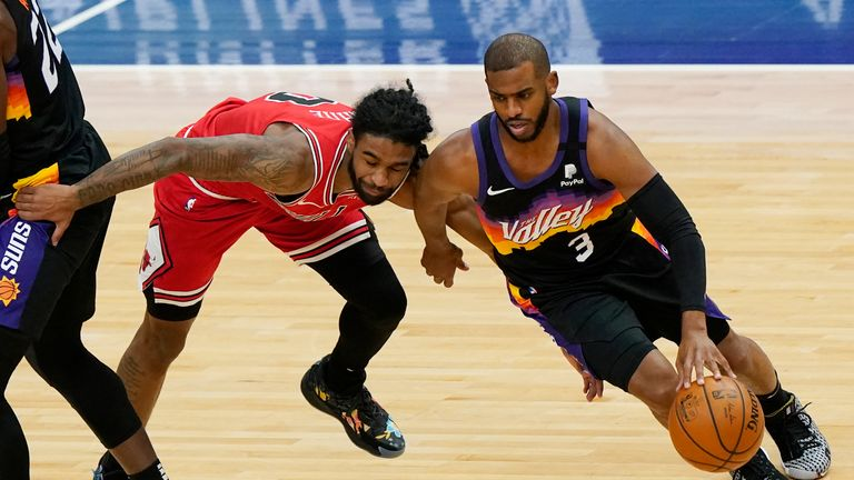 Phoenix Suns guard Chris Paul, right, drives against Chicago Bulls guard Coby White during the first half of an NBA basketball game in Chicago, Friday, Feb. 26, 2021. (AP Photo/Nam Y. Huh)