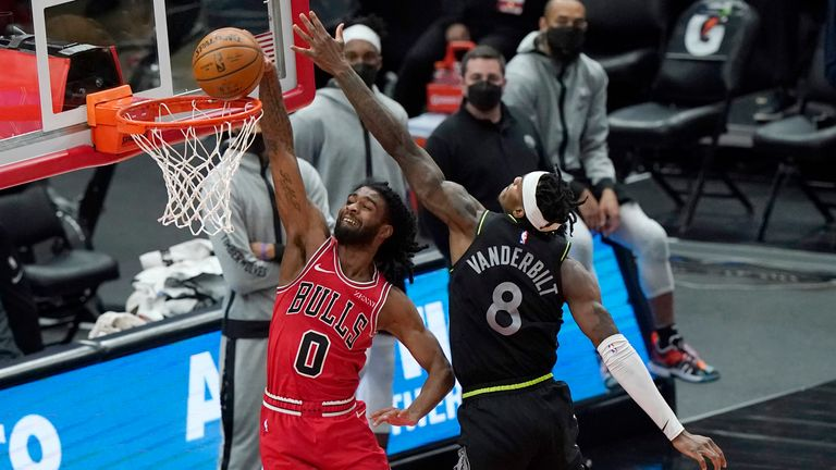 Chicago Bulls guard Coby White, left, dunks against Minnesota Timberwolves forward Jarred Vanderbilt during overtime of an NBA basketball game in Chicago, Wednesday, Feb. 24, 2021. The Bulls won 133-126 in overtime. (AP Photo/Nam Y. Huh)