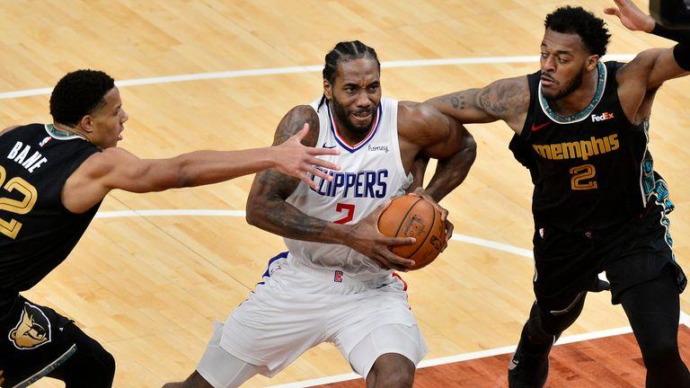 Los Angeles Clippers forward Kawhi Leonard (2) drives between Memphis Grizzlies guard Desmond Bane (22) and center Xavier Tillman (2) during the second half of an NBA basketball game Friday, Feb. 26, 2021, in Memphis, Tenn. (AP Photo/Brandon Dill)