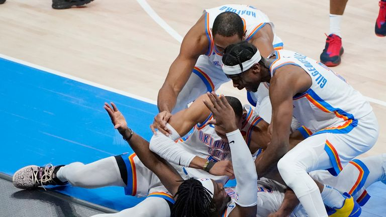 Oklahoma City Thunder's Darius Bazley, Al Horford and Shai Gilgeous-Alexander, clockwise from left, rush to celebrate with Luguentz Dort, bottom, after he hit the game-winning shot in the team's NBA basketball game against the San Antonio Spurs, Wednesday, Feb. 24, 2021, in Oklahoma City. (AP Photo/Sue Ogrocki)