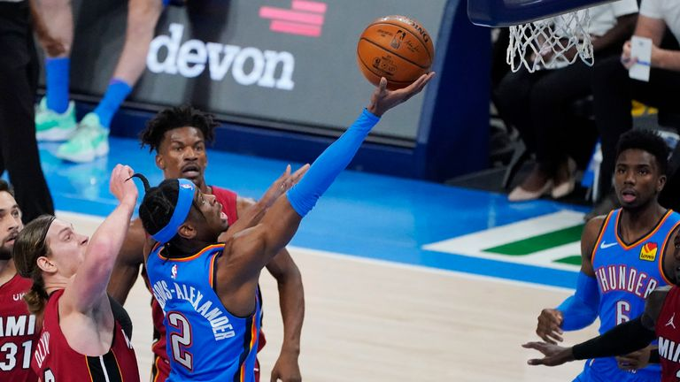 Oklahoma City Thunder guard Shai Gilgeous-Alexander (2) shoots in front of Miami Heat forward Kelly Olynyk, left, and forward Jimmy Butler, rear, in the first half of an NBA basketball game Monday, Feb. 22, 2021, in Oklahoma City.