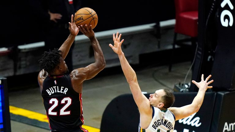 Miami Heat forward Jimmy Butler (22) shoots over Utah Jazz forward Bojan Bogdanovic (44) during the second half of an NBA basketball game, Friday, Feb. 26, 2021, in Miami. (AP Photo/Lynne Sladky)