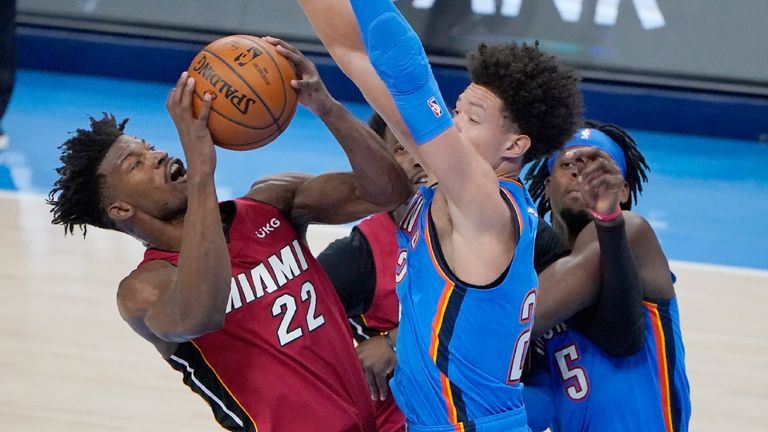 Miami Heat forward Jimmy Butler (22) is fouled by Oklahoma City Thunder center Isaiah Roby, center, in the second half of an NBA basketball game Monday, Feb. 22, 2021, in Oklahoma City.