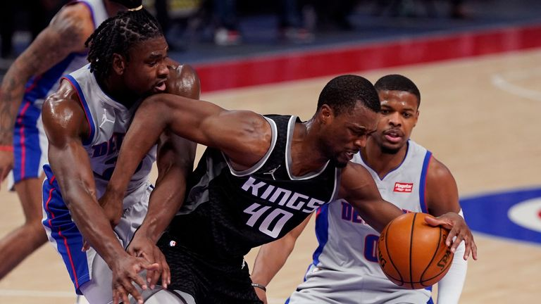 Sacramento Kings forward Harrison Barnes (40) is fouled by Detroit Pistons center Isaiah Stewart, left, next to Detroit Pistons guard Dennis Smith Jr. (0) during the first half of an NBA basketball game, Friday, Feb. 26, 2021, in Detroit. (AP Photo/Carlos Osorio)