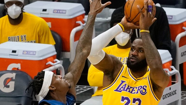 Los Angeles Lakers' LeBron James (23) shoots as Minnesota Timberwolves' Jarred Vanderbilt (8) defends in the first half of an NBA basketball game, Tuesday, Feb. 16, 2021, in Minneapolis.