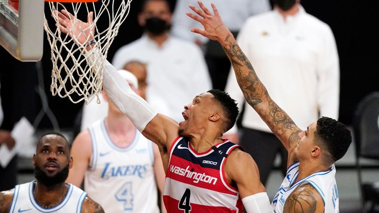 Washington Wizards guard Russell Westbrook, second from right, shoots as Los Angeles Lakers forward Kyle Kuzma, right, defends along with forward LeBron James during overtime in an NBA basketball game Monday, Feb. 22, 2021, in Los Angeles. The Wizards won 127-124 in overtime.
