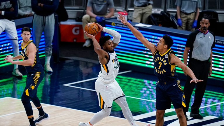 Utah Jazz guard Donovan Mitchell (45) makes a pass over Indiana Pacers guard Malcolm Brogdon (7) during the second half of an NBA basketball game in Indianapolis, Sunday, Feb. 7, 2021. (AP Photo/Michael Conroy)