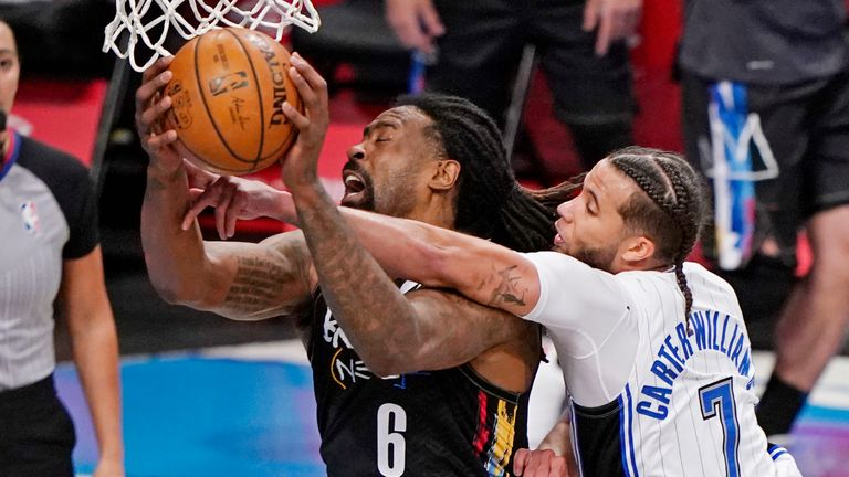 Orlando Magic guard Michael Carter-Williams (7) gets his hand caught as Brooklyn Nets center DeAndre Jordan (6) goes up to shoot beneath the basket during the third quarter of an NBA basketball game, Thursday, Feb. 25, 2021, in New York.