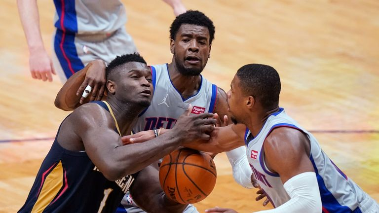 New Orleans Pelicans forward Zion Williamson (1) is fouled as he goes to the basket against Detroit Pistons guards Dennis Smith Jr., middle, and Josh Jackson during the second half of an NBA basketball game in New Orleans, Wednesday, Feb. 24, 2021. (AP Photo/Gerald Herbert)
