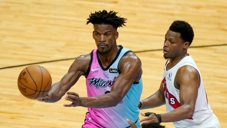 Miami Heat forward Jimmy Butler, left, passes as Toronto Raptors guard Kyle Lowry defends during the second half of an NBA basketball game, Wednesday, Feb. 24, 2021, in Miami. (AP Photo/Lynne Sladky)