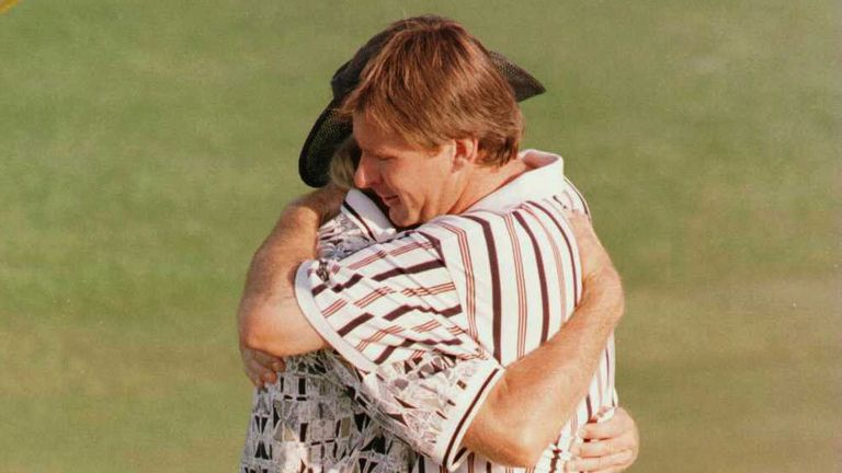 Faldo hugs Norman on the 18th green after wrapping up the victory