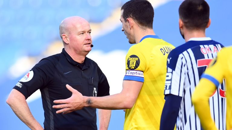 Players surround referee Lee Mason following confusion over Brighton's disallowed goal