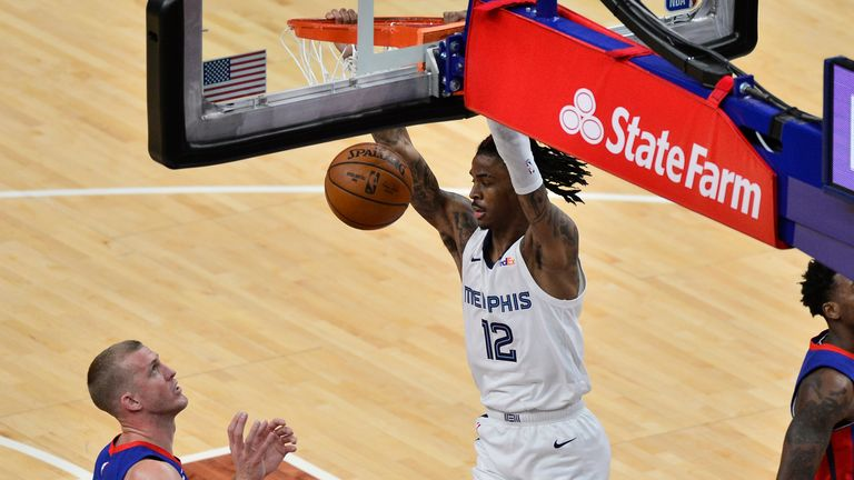Memphis Grizzlies guard Ja Morant dunks next to Detroit Pistons center Mason Plumlee