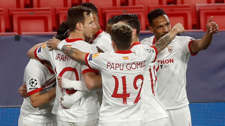 Sevilla players celebrate after Suso scored his side's opening goal during the Champions League, round of 16, first leg soccer match between Sevilla and Borussia Dortmund at the Ramon Sanchez Pizjuan stadium in Seville, Spain, Wednesday, Feb. 17, 2021. (AP Photo/Angel Fernandez)
