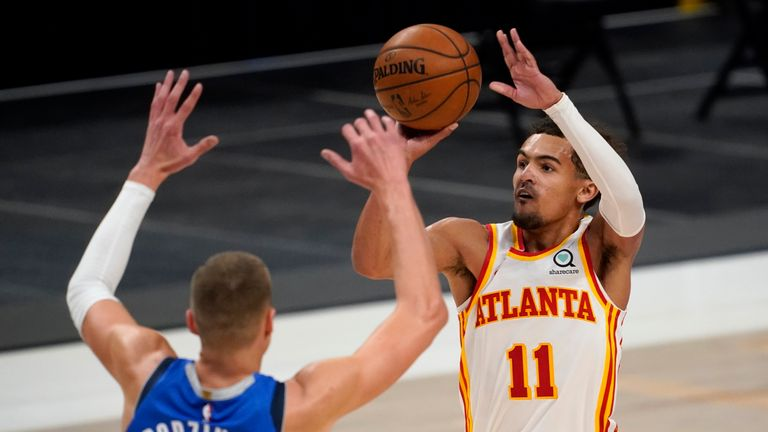 Dallas Mavericks' Kristaps Porzingis defends as Atlanta Hawks guard Trae Young attempts a three-point basket