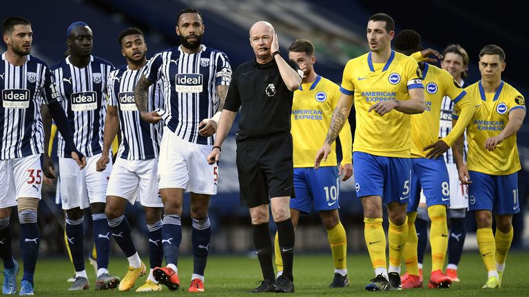 Players from both teams surround referee Lee Mason following confusion over Brighton's disallowed goal