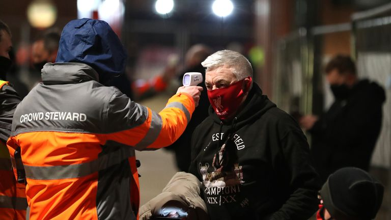 A Liverpool fan has his temperature checked before attending a Premier League match at Anfield